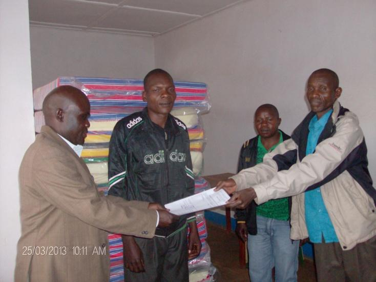 Ezati (left) hands over the invoice in front of the Avari Health Centre Chairperson (centre left) to the nurse in charge (right).